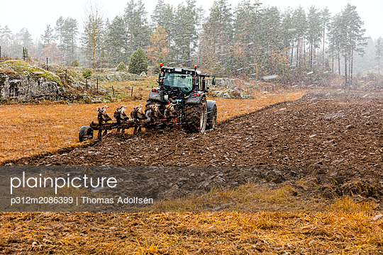 Tractor plowing field - p312m2086399 by Thomas Adolfsén