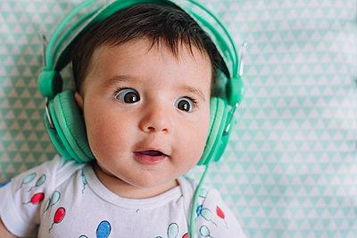 Portrait of amazed baby girl with headphones - p300m1460121 by Gemma Ferrando