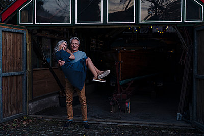 Senior man carrying his wife in front of boathouse - p300m2155022 by Gustafsson