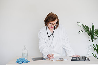 Female doctor with digital tablet writing on paper on clipboard at desk in hospital - p300m2274513 by Eva Blanco