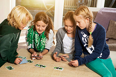 Four children playing card game in living room - p300m873911f by Gabi Dilly