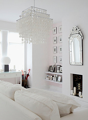 All white living room with decorative light shade, artwork and silver embossed mirror - p3493243 by Brent Darby