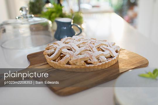 Fresh homemade baked lattice apple pie on cutting board - p1023m2208353 by Sam Edwards