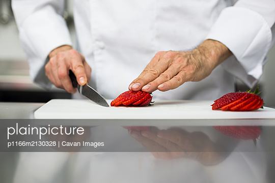 Chef slicing strawberries with kitchen knife - p1166m2130328 by Cavan Images