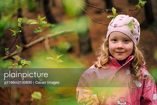 Cute blonde child smiling at camera in forest - p1166m2130830 by Cavan Images