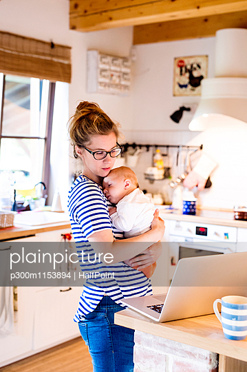 Mother with baby in kitchen looking at laptop - p300m1153894 by HalfPoint