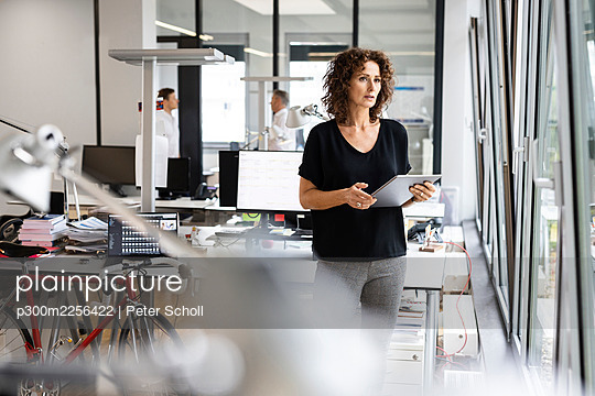 Businesswoman holding digital tablet while standing with colleague in background at open plan office - p300m2256422 by Peter Scholl