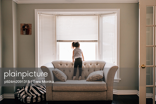 Girl standing on sofa looking through living room window, rear view - p924m2091315 by Sara Monika