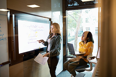Businesswomen strategizing in conference room meeting - p1192m2062427 by Hero Images
