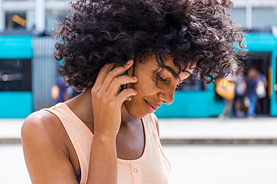 Germany, Frankfurt, portrait of smiling young woman with curly hair on the phone - p300m2030345 by Tom Chance