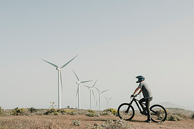 Spain, Lanzarote, mountainbiker on a trip in desertic landscape with wind turbines in background - p300m2102581 by Hernandez and Sorokina
