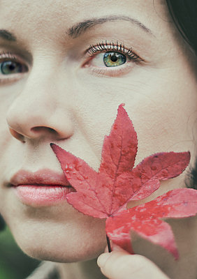 Woman holding leaf close to face - p577m954661 by Mihaela Ninic