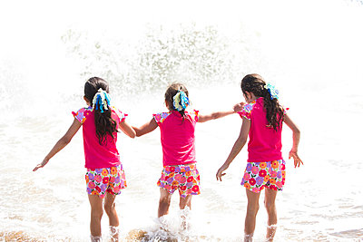 Back View of Girls in Matching Outfit Walking into the Sea - p669m806490 by Kelly Davidson