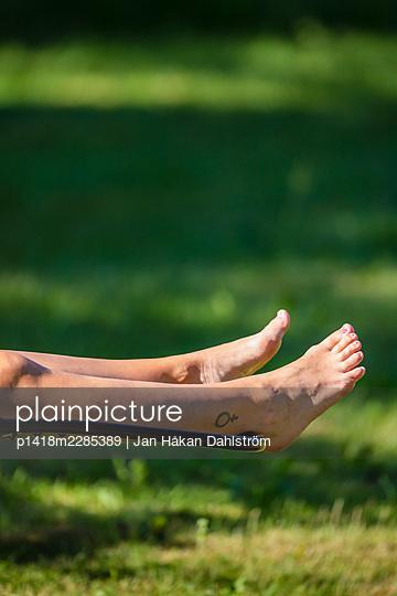 Woman's legs on sun lounger - p1418m2285389 by Jan Håkan Dahlström