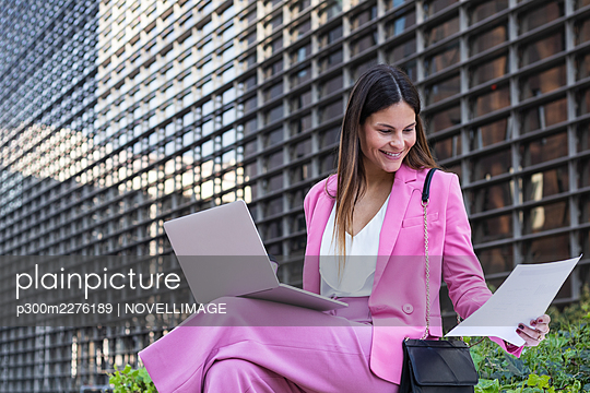 Smiling entrepreneur checking paper while sitting with laptop on lap - p300m2276189 by NOVELLIMAGE