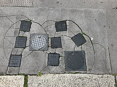 Water tap covers in a pavement - p1048m2016464 by Mark Wagner