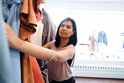 Woman shopping in clothing store - p1192m2110009 by Hero Images