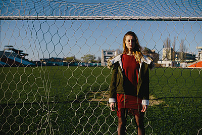 Portrait of girl in a red dress on the background fence mesh and playing field - p1363m1332313 by Valery Skurydin
