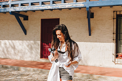 Woman smiling while holding camera at village during sunny day - p300m2282413 by Manu Reyes