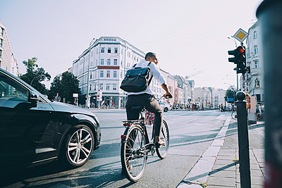 Full length of male entrepreneur riding bicycle on road in city against sky - p426m2169569 by Maskot