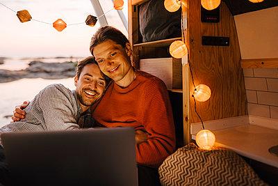 Man embracing boyfriend while watching movie on laptop in camping van - p426m2296129 by Maskot