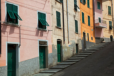 Buildings with green doors and shutters line the street; Riomaggiore, Liguria, Italy - p442m1033517f by Jenna Szerlag