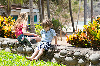Caucasian brother and sister sitting on stone wall at beach - p555m1305356 by Marc Romanelli