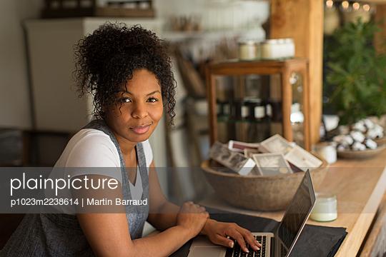 Portrait confident female shop owner using laptop in plant nursery - p1023m2238614 by Martin Barraud