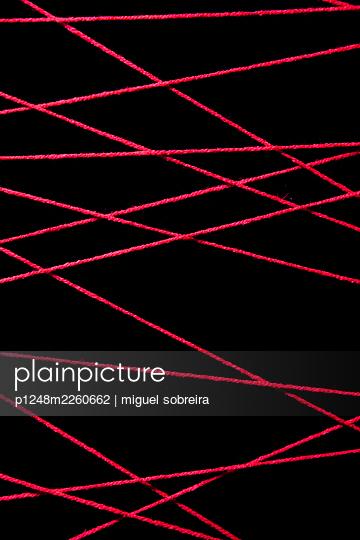 Red woolen threads against black background - p1248m2260662 by miguel sobreira
