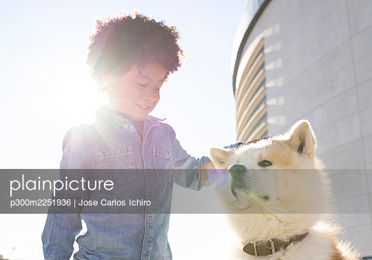 Smiling boy playing with pet dog while standing outdoors during sunny day - p300m2251936 by Jose Carlos Ichiro