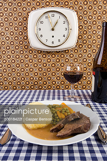 A plate of food with a glass and bottle of wine - p3018422f by Caspar Benson