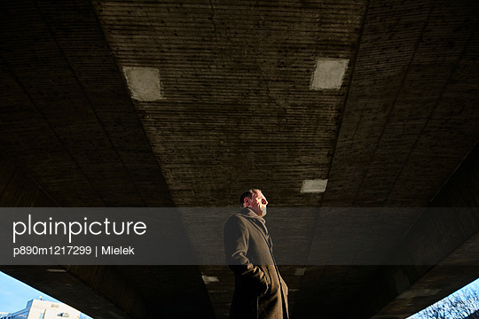 Man in coat standing under bridge - p890m1217299 by Mielek