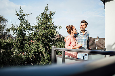 Mature couple looking at each other and smiling while standing in balcony on sunny day - p300m2243670 by Joseffson