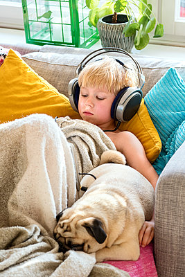 Boy with headphones on sofa - p312m1557268 by Sara Winsnes