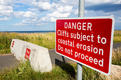 Warning sign at collapsed coastal road, Skipsea, Yorkshire, England, UK - p343m2000035 by Ashley Cooper