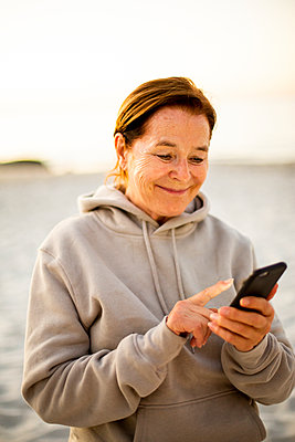 Woman using smartphone - p975m2056947 by Hayden Verry