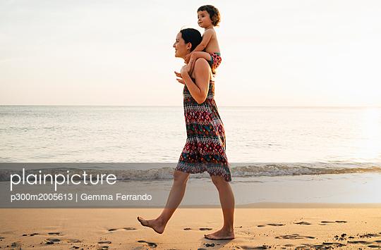 Thailand, Krabi, Koh Lanta, Mother with little daughter on her shoulders on the beach at sunset - p300m2005613 von Gemma Ferrando