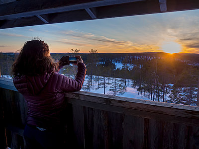 Rear view of woman photographing snow covered landscape with mobile phone while standing in balcony at tourist resort - p1166m2060750 by Cavan Social