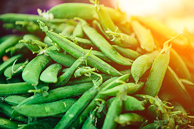 Stack of green peas at Farmers' market - p1166m2194021 by Cavan Images