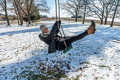 Smiling woman on swing in snow - p1427m2163632 by Steve Smith