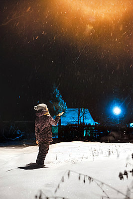 Girl catches snowflakes with her hands - p1642m2222204 by V-fokuse