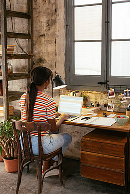 Back view of young woman sitting at desk in a loft working on laptop - p300m1581256 von Bonninstudio