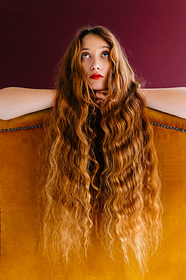 Young female fashion model with long brown wavy hair leaning on golden chair while looking up against colored background - p300m2199534 by Tania Cervián
