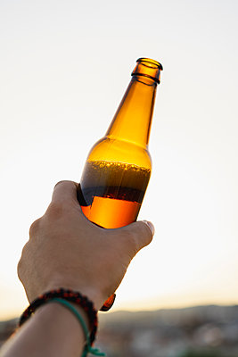 Man holding beer bottle during sunset - p300m2298801 by VITTA GALLERY