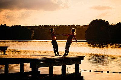 Women practicing acro yoga on tranquil sunset lake dock - p301m2075541 by Sven Hagolani