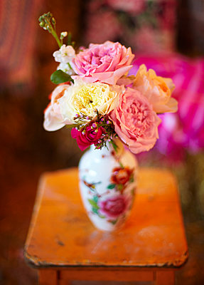Vase of cut flowers on orange side table - p349m2167857 by Sussie Bell