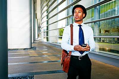 Black businessman using cell phone outside office building - p555m1312294 by Peathegee Inc