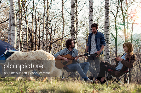 Friends camping in forest with man playing guitar