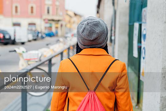 Italy, Milan, Rear view of woman in orange coat walking on sidewalk - p924m2292527 by Eugenio Marongiu