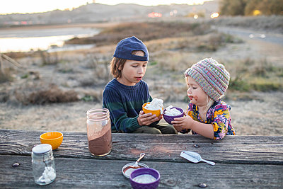 Adorable siblings drinking hot cocoa by wooden table at twilights - p1166m2095159 by Cavan Images
